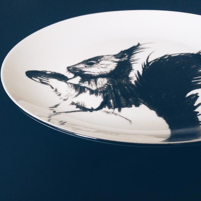 Teller mit auf schwarzem Untergrund mit einem schwarzen Eichhörnchen bemalt.