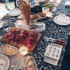 Schön gedeckter Tisch mit Käse- und Wurstplatten, Kerzen und verschiedenen Dips