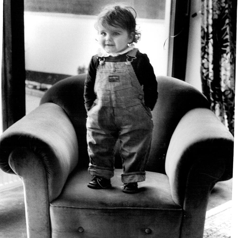 Kind auf einem Sessel in Latzhose, schwarz-weiß Bild aus den 80ern