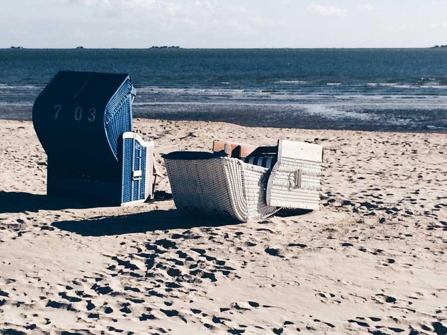 zwei Strandkörbe, einer davon umgefallen
