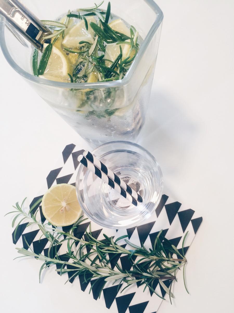 Karaffe mit Wasser, Rosmarin und Zitrone sowie zwei Gläser