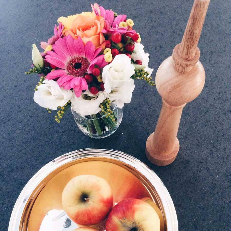 kleiner Blumenstrauß neben Schale mit Äpfeln und Pfeffermühle