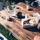 Holztisch auf einer grünen Wiese, eingedeckt mit Brot, Dips und Getränken