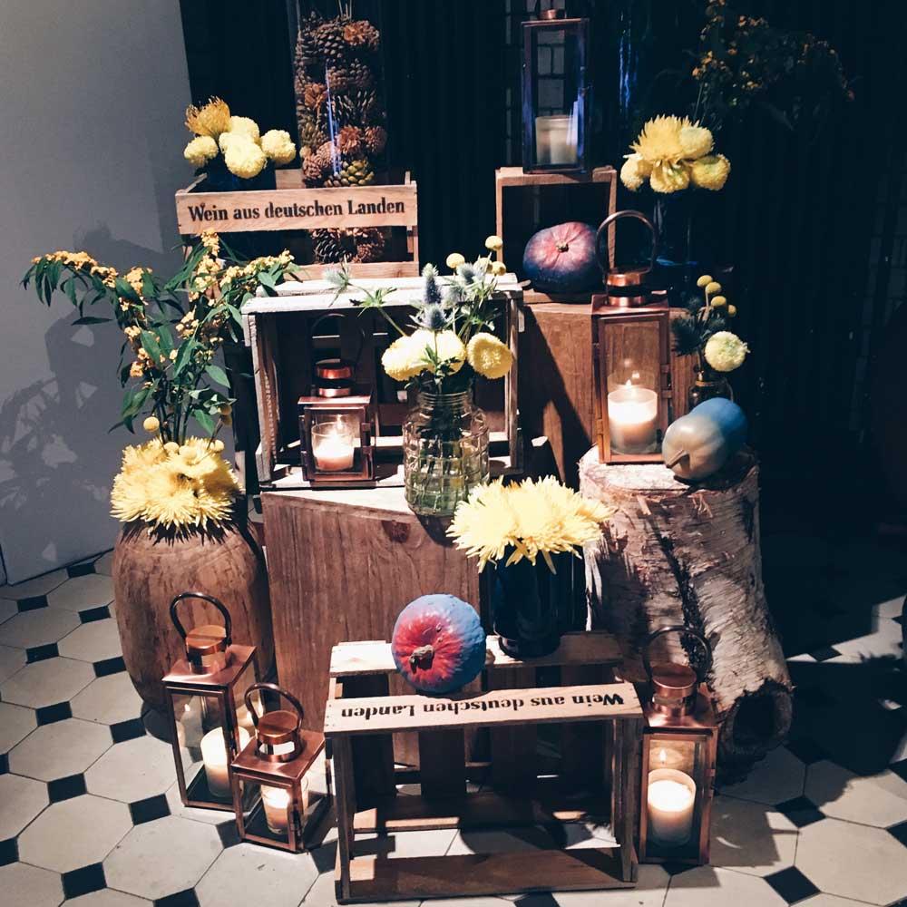 Eventdekoration mit Blumen in gelb, Kerzen, Kürbissen und Holzkisten