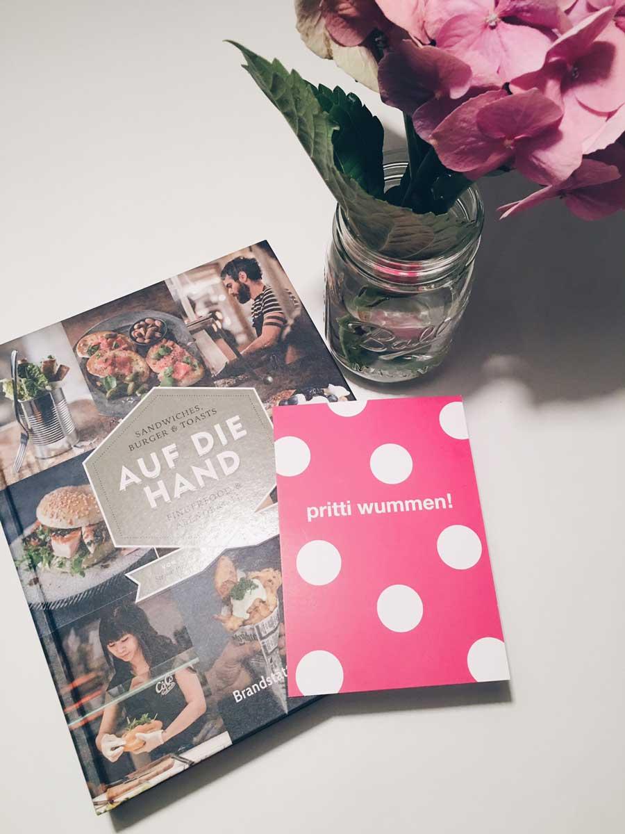 """Buch mit dem Titel """"Auf die Hand"""" neben einem Blumenstrauß und einer Karte mit der Aufschrift """"Pritti Wummen"""""""