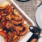 Auflaufform mit Kürbisstreifen und Currypaste auf einem gedeckten Tisch