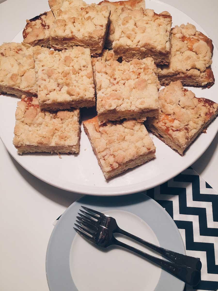 Tortenplatte mit vielen Stücken Aprikosen-Streuselkuchen