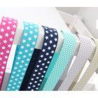 Verschiedene Bänder in Türkis, Pink, Blau und Grau über einer Stuhllehne