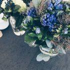 Zwei Blumenstraeusse in Glasvasen