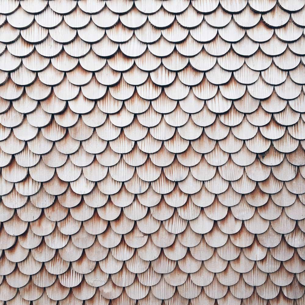 Holzfassade eines Hauses, die aus vielen, abgerundeten Holzstücken besteht