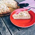 Rhabarberkuchen auf einer Platte, angeschnitten und Einzelstück im Vordergrund