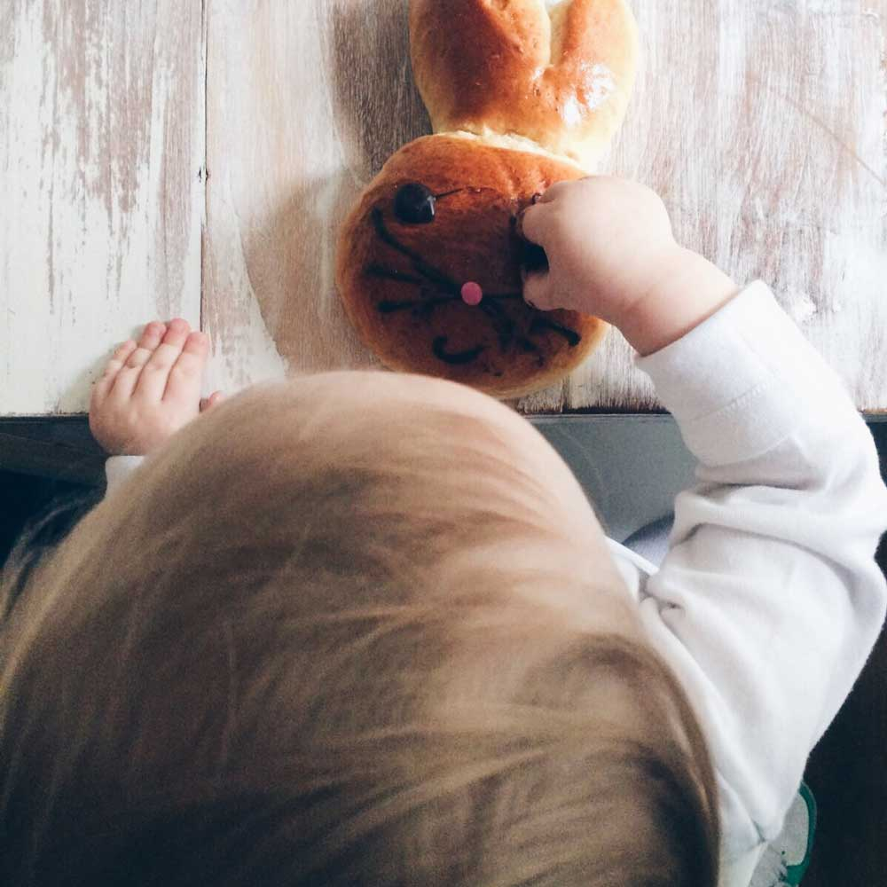 Die Nichte isst ein Hasenteilchen mit Schokoaugen