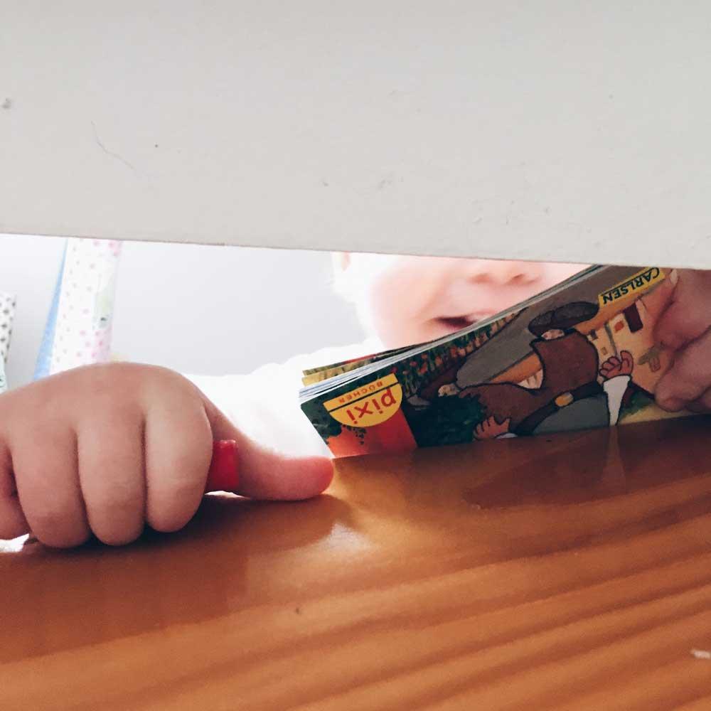 Kind schiebt Pixiebüchlein durch eine Treppestufe