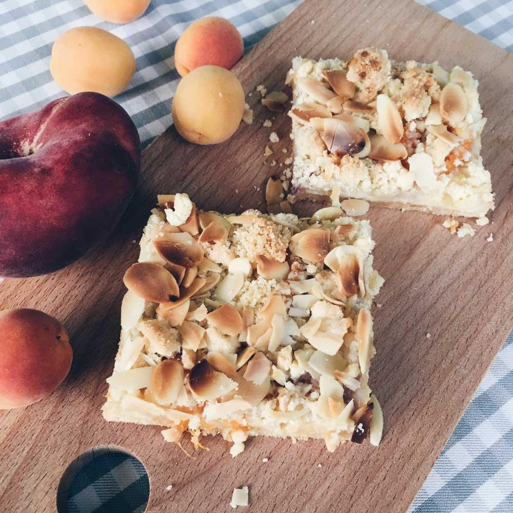 Zwei Stücke Aprikosen-Pfirsich-Streuselkuchen auf einem Brett, Obst daneben
