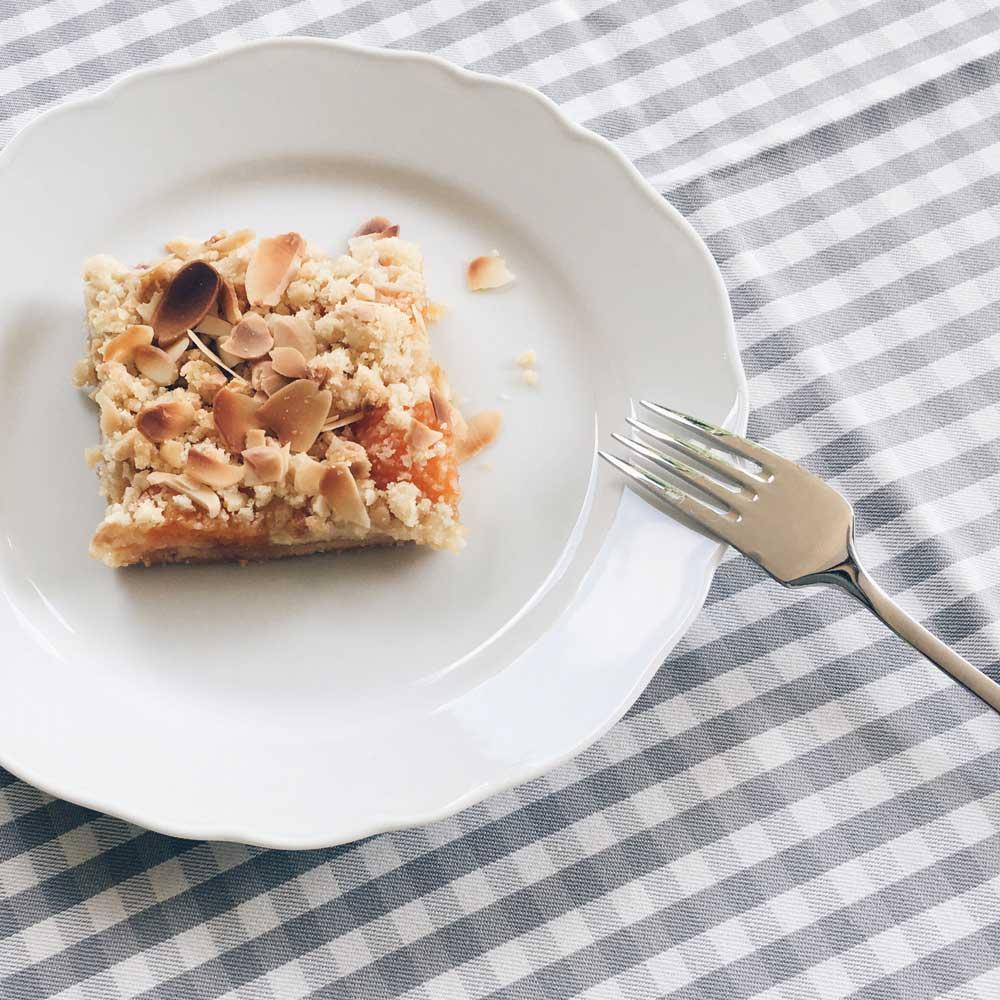 Ein Stück Aprikosen-Pfirsich-Streuselkuchen auf einem Teller