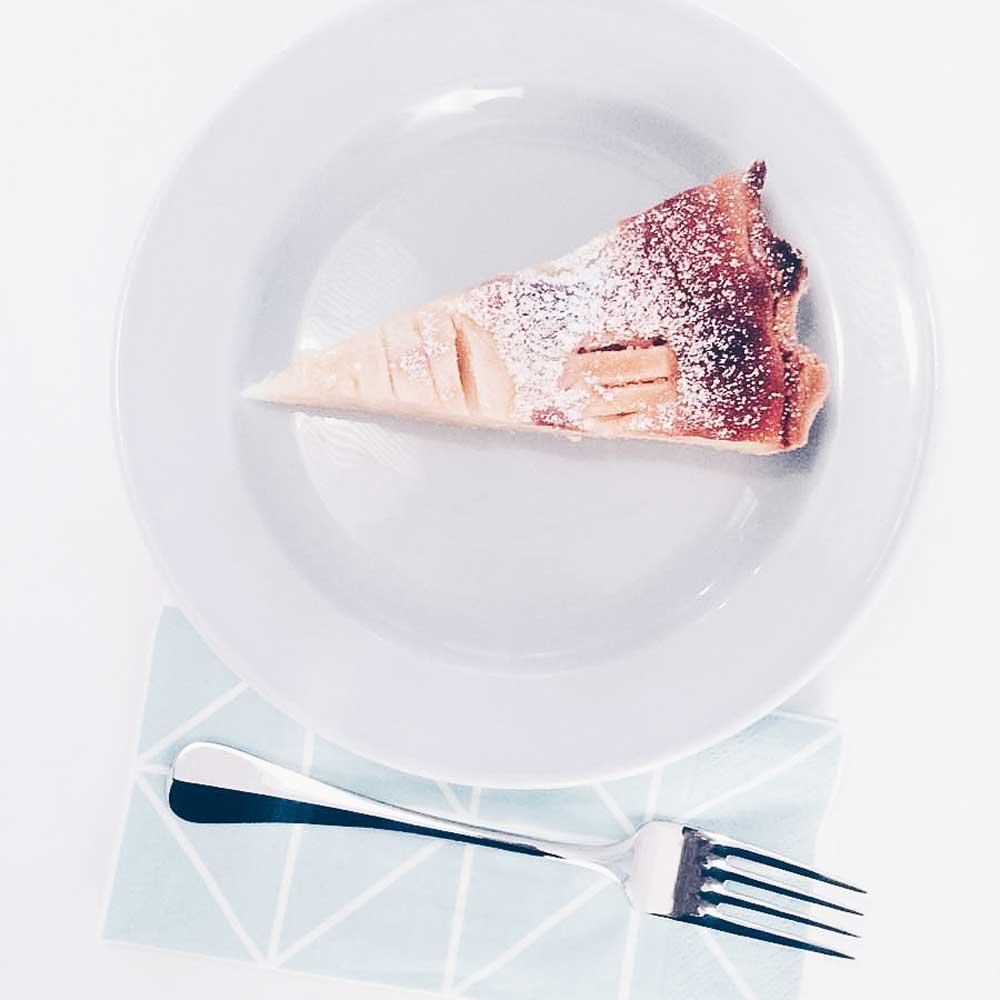 Teller mit einem Stück Apfeltarte und Serviette